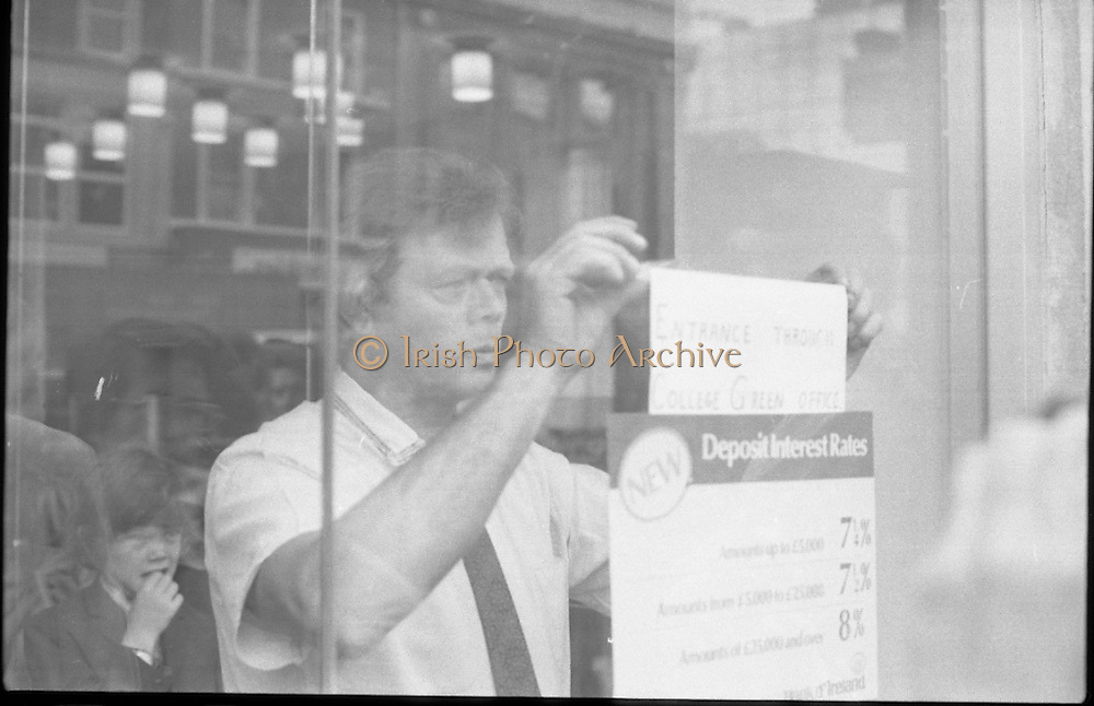 Fergus Rowan sits in at Bank of Ireland.  (J70)..1975..22.08.1975..08.22.1975..22nd August 1975..As a result of the 1970 bank strike which lasted for six months, the Rowan family business found itself in financial difficulties. During the strike the Rowans had had to accept cheques in good faith in order to stay in business. When the cheques came for settlement the bank refused as they stated that some were 'dodgy'. This put severe strain on the business which was eventually put into receivership.As part of the process the Rowan business beside the bank was put up for sale and was purchased by B.o I. Rowan was outraged and started a campaign against the bank which culminated in a sit in at the banks headquarters in Westmoreland St,Dublin. He also became a thorn in the side of the bank at the A.G.Ms raising many points...Mr Rowan is pictured adding his own notice to the bank door.