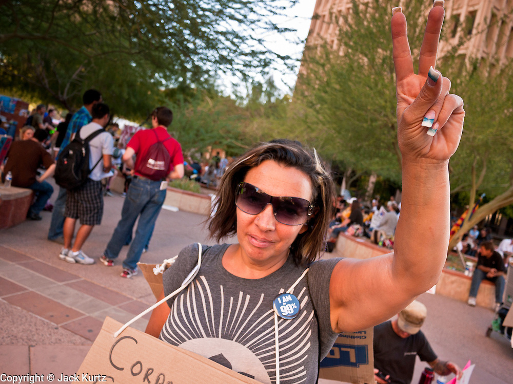 16 OCTOBER 2011 - PHOENIX, AZ: An Occupy Phoenix protester flashes a peace sign at passing cars during the protest in downtown Phoenix, AZ, Sunday. About 200 people continued the Occupy Phoenix protest in downtown Phoenix Sunday afternoon. The protest peaked Saturday afternoon at about 2,000 people. Nearly 50 people were arrested late Saturday night on misdemeanor trespassing charges when they tried to camp in a park near downtown and on Sunday the crowd dwindled to 200. Protesters hope to continue the protest through Monday by marching around downtown and picketing banks in the area.    PHOTO BY JACK KURTZ