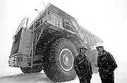 Wester truck in snowstorm with men discussing