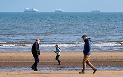 Portobello, Scotland, UK. 28 March, 2020. On the first weekend of the coronavirus lockdown the public were outdoors exercising and maintaining social distancing along Portobello beachfront promenade. Pictured People walking and jogging on beach with three cruise ships berthed in distance. Iain Masterton/Alamy Live News