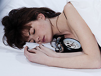 young woman in a white sheet bed on white background sleeping with her alarm clock