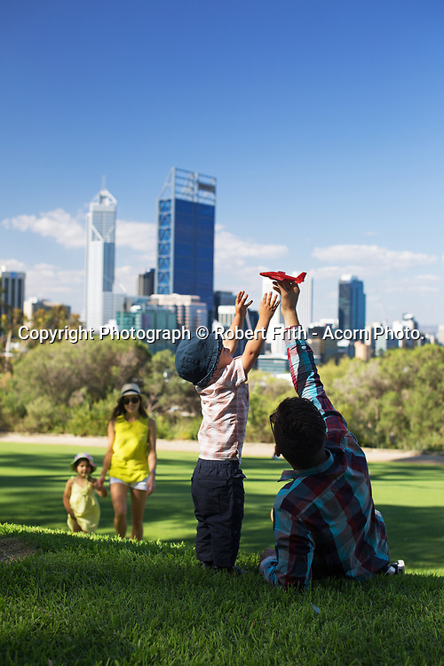 Family playing in Kings Park with the Perth CBD in the background