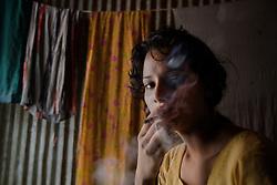 Sex worker Shetu, 17, smokes at brothel in Tangail, Bangladesh.