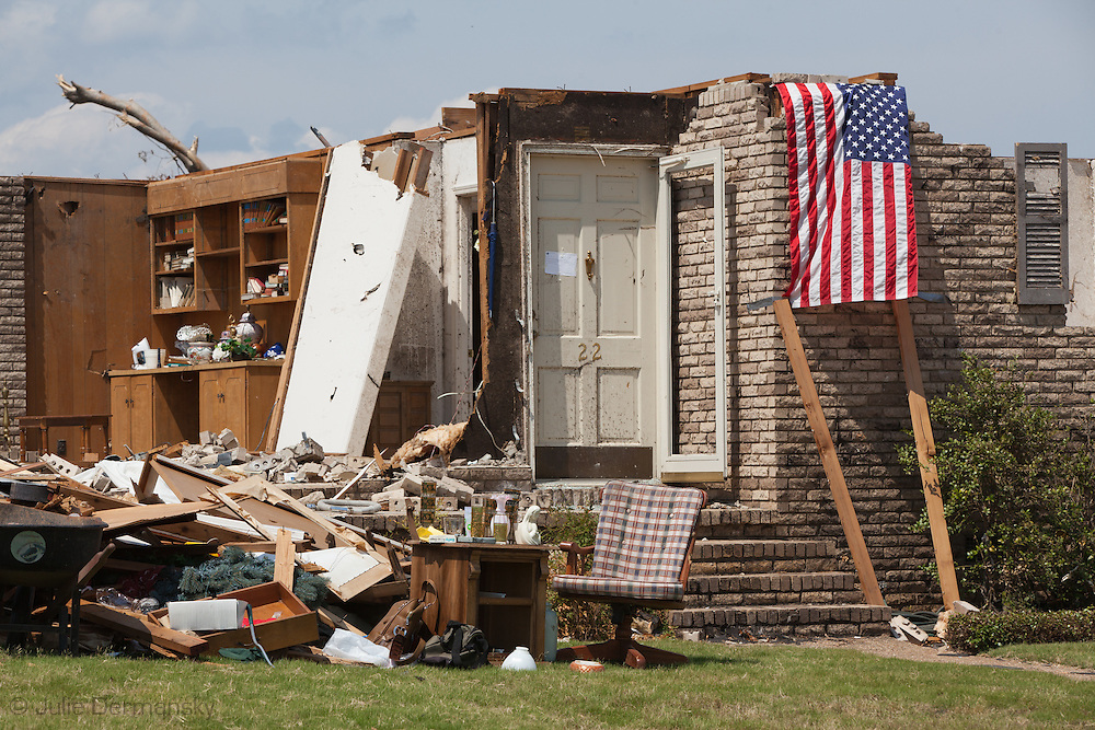 An American flag in front of a home totaled by a tornado in Alabama. Parts of Tuscaloosa , in west central Alabama  remain in a state of ruin  two weeks after it was hit by an F-4 ( possibly an F-5) tornado, one of an estimated 300 that struck Alabama and the neighboring states on April 27th , 2011.