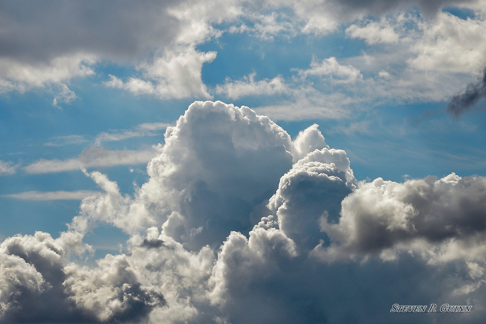 """I captured this image, as well as """"Clouds Rolling In"""" and """"Ominous Autumn Clouds"""", while I was in Rensselaer, Indiana on September 29th, 2016. What stood out the most about these cloud formations for me was how it looked like an explosion. I like how the light greys and whites are intertwined with the dark greys and blacks over several areas of the clouds to give the image great contrast and a foreboding look. I also like how the sunlight illuminates the sharply-defined edges in the center of the formation.<br /> <br /> Printed on Hahnemühle German Etching paper. Limited to 150 productions per size.<br /> <br /> Framed prints are available in 18"""" x 12"""", 24"""" x 16"""", 30"""" x 20"""", and 36"""" x 24"""" sizes."""