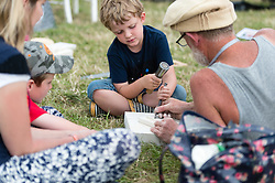 © Licensed to London News Pictures. 27/06/2015. Pilton, UK.  Festival atmosphere at Glastonbury Festival 2015 on Saturday Day 4 of the festival - a stone mason teaches young boys how to carve stone with their mother in the arts and crafts area.  This years headline acts include Kanye West, The Who and Florence and the Machine, the latter being upgraded in the bill to replace original headline act Foo Fighters. Photo credit: Richard Isaac/LNP