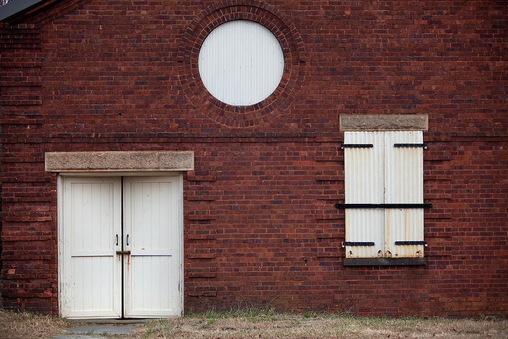 The wall of a storage facility with barn door and unusual window pattern at Fort Hancock Sandy Hook