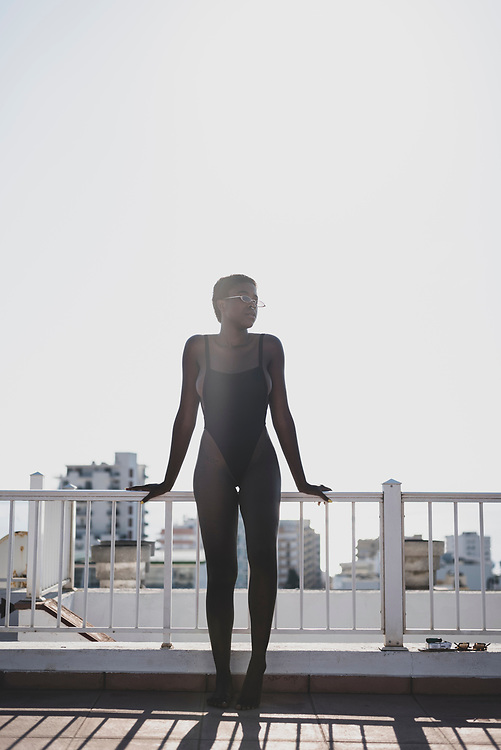 Sant Antoni de Portmany, Ibiza, Spain - August 3, 2018: Maria, from Madrid, stands in the afternoon sun on the rooftop of an apartment building in Sant Antoni (San Antonio), Ibiza.