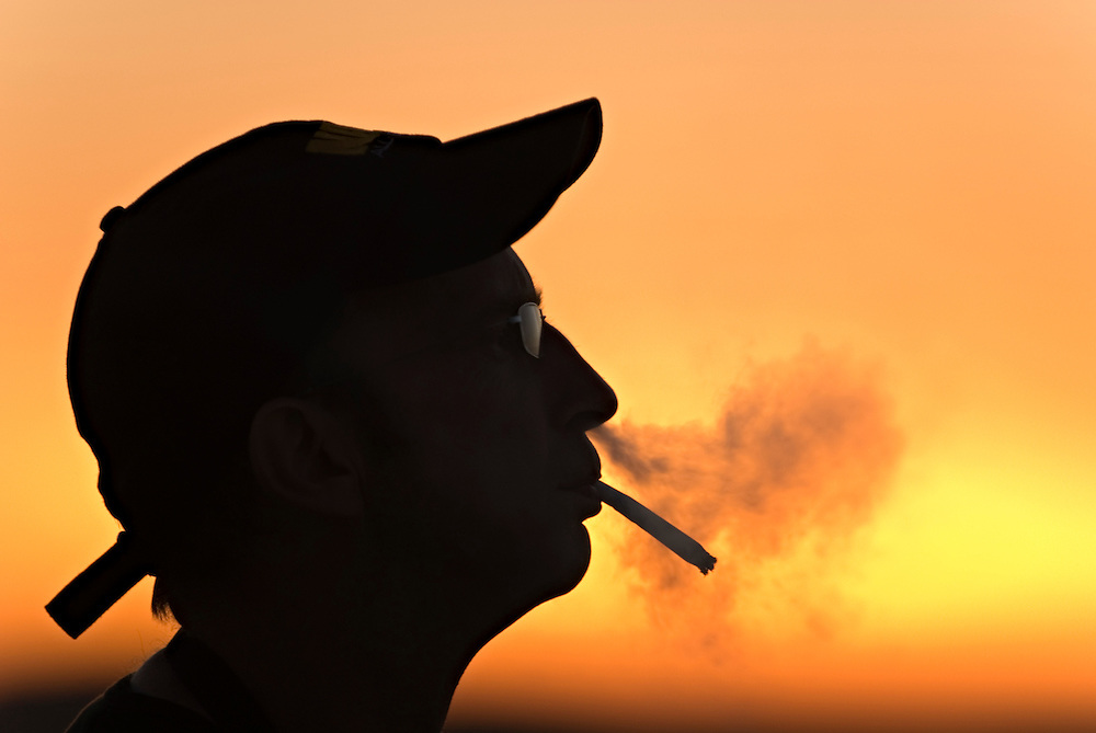 Ein Raucher bläst im Gegenlicht der Abendsonne den Rauch einer Zigarette durch die Nase aus. | a male cigarette smoker in silhouette  profile smoking during sun set