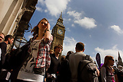 From a very low viewpoint, we see crowds of British citizens who to and fro beneath the Gothic tower of Big Ben in Parliament Square, London at almost 10 minutes past 2pm . Lots of people squeeze past each other during the closing stages of London's Marathon as the pavements is narrower when crowd barriers control numbers. A young lady finds her way through other passers-by as the clock tower rises at an angle, the perspective of the wide-angle lens' distortion. The female's t-shirt has a woman's face from the xx clothing brand. This is also election time and the people are subject to the democratic process as they elect an new leader to govern the state.