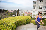 Een vrouw rent de trappen van een van de steile heuvels in San Francisco omhoog. In de achtergrond is de baaij van San Francisco te zien. De Amerikaanse stad San Francisco aan de westkust is een van de grootste steden in Amerika en kenmerkt zich door de steile heuvels in de stad.<br /> <br /> A woman runs at the stairs of a steep hill in San Francisco. In the background San Francisco Bay is visible. The US city of San Francisco on the west coast is one of the largest cities in America and is characterized by the steep hills in the city.