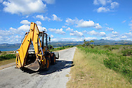 A Venieri backhoe loader drives down a road adjacent to the Caribbean Sea; The road connects the town of Trinidad to the nearby beach of Playa Ancon.