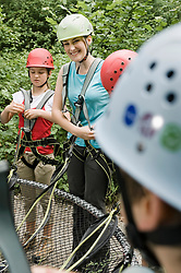Young woman and children preparing for climb crag, smiling