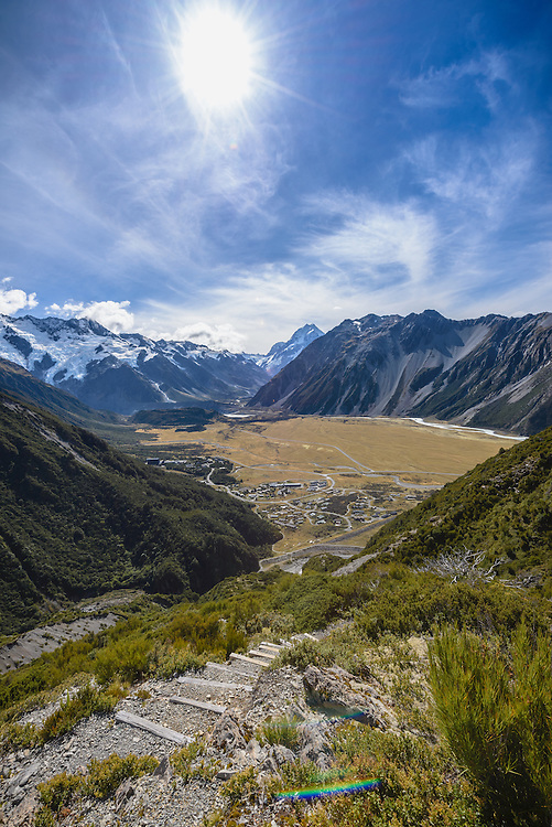 Elevated view of Mount Cook Village with blue sky and mountain range background