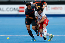 Netherlands' Glenn Schuurman (left) and England's Phil Roper during the Men's World Hockey League, semi-final match at Lee Valley Hockey Centre, London.