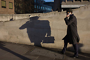 A man carrying a briefcase walks on the south side of London Bridge in Southwark, central London. As he makes his way uphill and alongside a slanted wall, his long shadow from winter afternoon shunshine is cast in front of him as a distorted form of his body. We still see the shape of his hat and the case on his right hand.