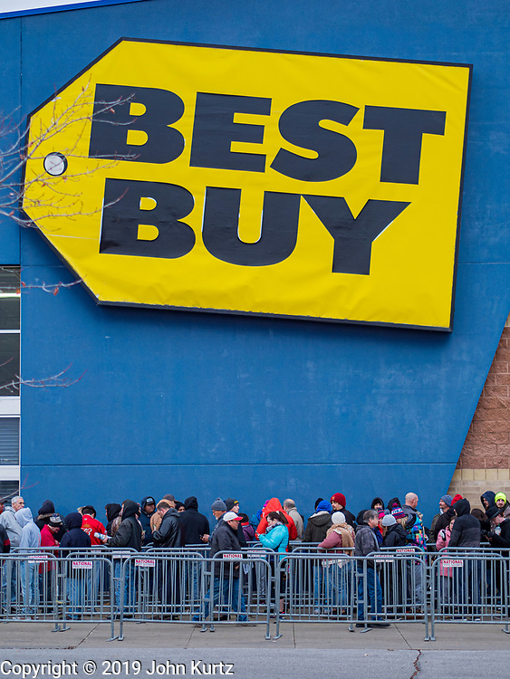 "28 NOVEMBER 2019 - ANKENY, IOWA: Holiday shoppers line up in front of the Best Buy in Ankeny Thursday evening. ""Black Friday"" is the unofficial start of the Christmas holiday shopping season and has traditionally thought to be one of the busiest shopping days of the year. Brick and mortar retailers, like Best Buy, are facing increased pressure from online retailers this year. Many retailers have started opening on Thanksgiving Day. Many Best Buy stores across the country opened at 5PM on Thanksgiving to attract shoppers with early ""Black Friday"" specials.           PHOTO BY JACK KURTZ"