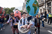 Extinction Rebellion activist playing the Earth sousaphone at the Marine Rebellion march on 6th September 2020 in London, United Kingdom. Ocean Rebellion, Sea Life Extinction, Animal Rebellion and Extinction Rebellion joined together to celebrate the biodiversity found in our seas, and to grieve at the destruction of the Earth's oceans and marine life due to climate breakdown and human interference, and the loss of lives, homes and livelihoods from rising sea levels. Extinction Rebellion is a climate change group started in 2018 and has gained a huge following of people committed to peaceful protests. These protests are highlighting that the government is not doing enough to avoid catastrophic climate change and to demand the government take radical action to save the planet.