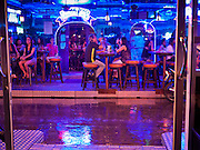 "12 JULY 2011 - BANGKOK, THAILAND:  People drink at a beer bar frequented by prostitutes and their customers on Soi Cowboy, a ""red light"" district in Bangkok, during a rainy season downpour. Prostitution in Thailand is illegal, although in practice it is tolerated and partly regulated. Prostitution is practiced openly throughout the country. The number of prostitutes is difficult to determine, estimates vary widely. Since the Vietnam War, Thailand has gained international notoriety among travelers from many countries as a sex tourism destination. One estimate published in 2003 placed the trade at US$ 4.3 billion per year or about three percent of the Thai economy. It has been suggested that at least 10% of tourist dollars may be spent on the sex trade. According to a 2001 report by the World Health Organisation: ""There are between 150,000 and 200,000 sex workers (in Thailand).""  PHOTO BY JACK KURTZ"