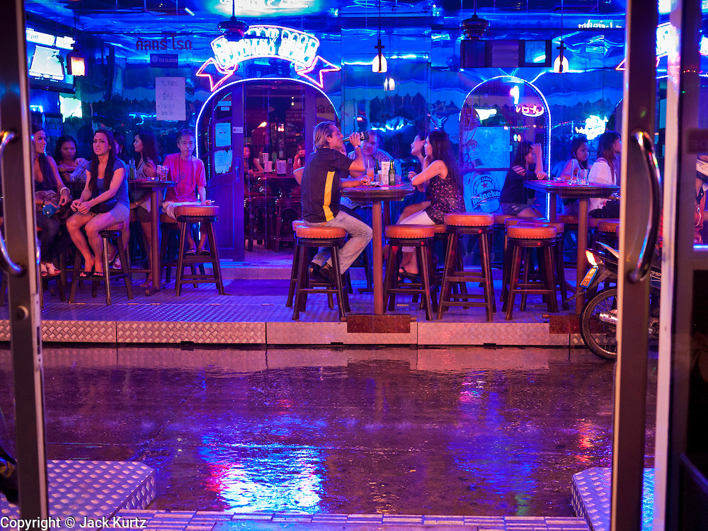 """12 JULY 2011 - BANGKOK, THAILAND:  People drink at a beer bar frequented by prostitutes and their customers on Soi Cowboy, a """"red light"""" district in Bangkok, during a rainy season downpour. Prostitution in Thailand is illegal, although in practice it is tolerated and partly regulated. Prostitution is practiced openly throughout the country. The number of prostitutes is difficult to determine, estimates vary widely. Since the Vietnam War, Thailand has gained international notoriety among travelers from many countries as a sex tourism destination. One estimate published in 2003 placed the trade at US$ 4.3 billion per year or about three percent of the Thai economy. It has been suggested that at least 10% of tourist dollars may be spent on the sex trade. According to a 2001 report by the World Health Organisation: """"There are between 150,000 and 200,000 sex workers (in Thailand).""""  PHOTO BY JACK KURTZ"""