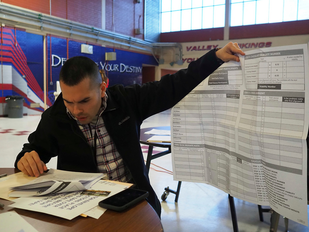 A caucus precinct chair reviews the caucus match poster rules prior to the start of the caucus at Valley High School in Las Vegas, Nevada.