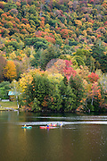 Four people kayak on reservoir in Fall.