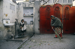 Back yard of middleclass family in Gobindigarh; Punjab; India; with mother sweeping the yard while young girl gets water from pump,