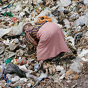 A woman collects rubbish for recycling at the dump; plastic, clothes, charcoal, metal even food for humans and livestock are all reclaimed for cash or personal use . <br /> <br /> Making a living from the local dumps in Eldoret is no easy job; disease, injury, substance abuse and even the threat of violence is an everyday reality for the people who live and work here.  The average wage is around $1.5 a day. These pictures were taken with the help of charity Mary's Meals who are hoping to break the cycle of poverty by providing free school meals.