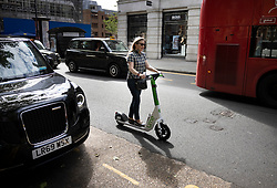 © Licensed to London News Pictures. 07/06/2021. London, UK. A tourist who gave her name as Nina rides a Lime e-scooter round Sloane Square on the first day of availability. E-scooters have become available to hire in four boroughs in London in a trial starting today. Photo credit: Peter Macdiarmid/LNP