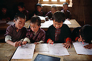 Bhutanese language writing class at the school in Gaselo, Bhutan. The school is an hour's walk from Shingkhey Village. From Peter Menzel's Material World Project.
