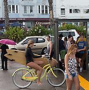 Bondi Beach Sydney australia. Girl riding her bike in the rain with her surfboard under her arm on Campbell Pde Bondi.