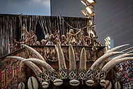 Performers in costume stand at dawn on a parade float depicting slavery as the float begins its journey past thousands of spectators in the Sambodrome during Carnival in Rio de Janeiro, Brazil. (March 4, 2019)