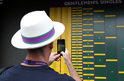 A spectator takes a picture of the Gentlemen's singles draw on day seven of the Wimbledon Championships at the All England Lawn Tennis and Croquet Club, Wimbledon. PRESS ASSOCIATION Photo. Picture date: Monday July 9, 2018. See PA story TENNIS Wimbledon. Photo credit should read: Steven Paston/PA Wire. RESTRICTIONS: Editorial use only. No commercial use without prior written consent of the AELTC. Still image use only - no moving images to emulate broadcast. No superimposing or removal of sponsor/ad logos. Call +44 (0)1158 447447 for further information.
