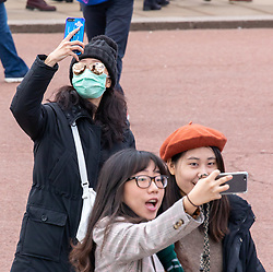 © Licensed to London News Pictures. 11/03/2020. London, UK. A young women in a mask does a selfie during the Changing of the Guards at Buckingham Palace as Health Minister, Nadine Dorries goes in to self-isolation after catching Covid19. Yesterday British Airways cancelled all flights to and from Italy as fears over the Coronavirus disease continues. Photo credit: Alex Lentati/LNP