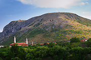 View of A cross on a hilltop near the city. Just beneath the mountain are several mosques. Historic town of Mostar. Federation Bosne i Hercegovine. Bosnia Herzegovina, Europe.