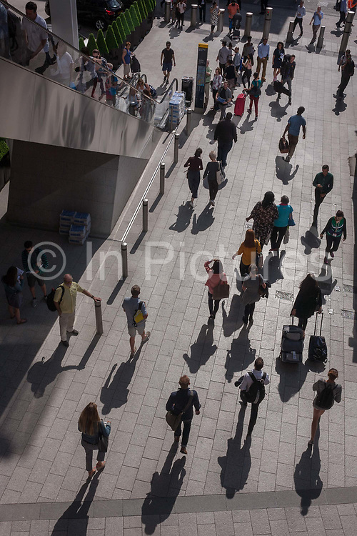 An aerial view of pedestrians and their shadows in strong sunshine, on 1st September 2016, in Southwark, south London, England UK. Members of the public walk in the bright light from reflected light of plate glass.