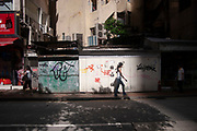 Young woman walks past a wall covered in graffiti in Wan Chai district of Hong Kong, China. Graffiti is yet another signifier of westernaisation in this mixed cultural city.