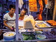 24 MARCH 2017 - BANGKOK, THAILAND: A noodle soup vendor (left) prepares an order for a regular customer (center) at his cart on Sukhumvit Soi 69 (Phra Khanong). He is facing probable eviction by 17 April. Food cart vendors along Sukhumvit Road between Sois 55 (Thong Lo) and 69 (Phra Khanong) in Bangkok have been told by city officials that they have to leave the area by 17 April. It's a part of an effort by Bangkok city government, supported by the ruling junta, to take back the city's sidewalks. The evictions in the area are the latest in mass evictions of Bangkok street food vendors after similar actions elsewhere on Sukhumvit, in the Ari area, in Silom/Patpong and Ratchaprasong neighborhoods. The vendors in Thong Lo/Phra Khanong are popular with local office workers because most of the formal restaurants in the area serve foreign tourists and upper class Thais and are very expensive. The street food carts serve meals starting at about 35Baht ($1US). The city has not announced if they will provide alternative locations for the carts.     PHOTO BY JACK KURTZ
