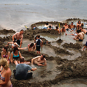 Tourists dig pools and relax in the hot water on Hot Water Beach a beach on the east coast of the Coromandel Peninsula, North Island, New Zealand. Its name comes from underground hot springs which filter up through the sand between the high and low water tidal reaches. The beach is a popular destination both for locals and tourists visiting New Zealand. Photo Tim Clayton