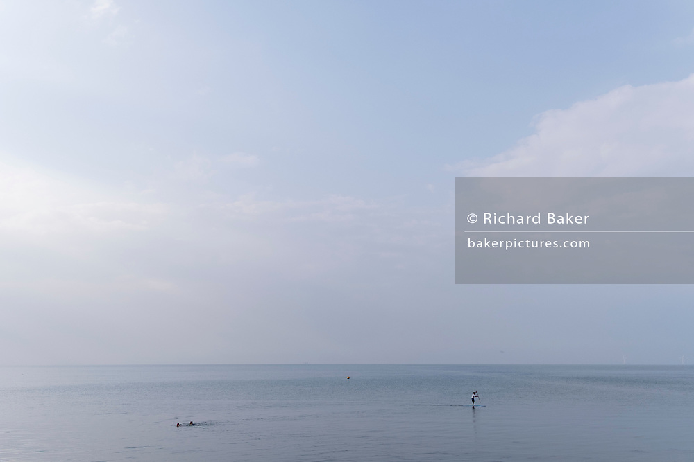Two sea swimmers and a paddleboarder cross a calm seacape, the high-tide waters of the Thames Estuary, on 26th July 2021, in Whitstable, Kent, England.