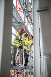Construction workers verifying the building site on scaffold, Munich, Bavaria, Germany
