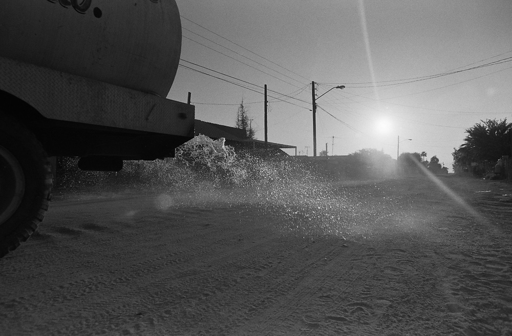 Watering the dirt streets in the morning to help keep dust down.