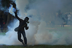 May 17, 2017 - Colombo, Sri Lanka - A Sri Lankan university student wearing a mask throws back a tear gas canister fired by police to disperse them during a protest. Police fired tear gas at thousands of students protesting against a private medical university they say could jeopardize the nation's tradition of state-funded education. (Credit Image: © Tharaka Basnayaka/NurPhoto via ZUMA Press)