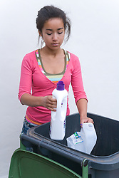 Teenage girl putting plastic containers into recycling wheelie bin ready for collection,