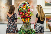 The Affordable Art Fair opens in Hampstead and runs until 15 June. Here viewing a face made from fruit and veg (inspired by the painting of Guiseppe Arcimbaldo), the work of  the Hampstead School of art. The event offers visitors a chance to purchase work from over 100 galleries at prices between £40 and £4,000. Hampstead Heath, London UK 11 June 2014. Guy Bell, 07771 786236, guy@gbphotos.com