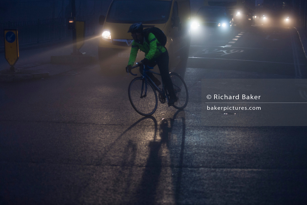 Cyclist crosses commuter junction in front of traffic at dawn on a foggy morning in south London.