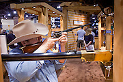 16 MAY 2009 -- PHOENIX, AZ: A man aims a replica Colt carbine in the Stoeger booth at the NRA convention in Phoenix Saturday. About 60,000 people were expected to attend the trade show at the 138th annual National Rifle Association Annual Meeting in the Phoenix Convention Center in Phoenix, AZ. Photo by Jack Kurtz