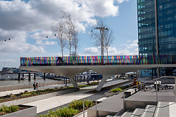 © Licensed to London News Pictures. 27/03/2021. London, UK. The new art installation titled Hundreds and Thousands by artist Liz West for The Tide. The outdoor art work is installed on the new elevated riverside trail, The Tide, on the Greenwich Peninsula. 700m of the walkways glass balustrades are covered by a ribbon of colour. Hundreds and Thousands is presented by NOW Gallery.<br />  credit: Ray Tang/LNP