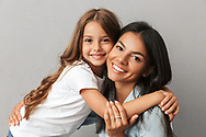 Photo of attractive woman with little daughter smiling and hugging together isolated over gray background