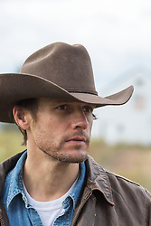 rugged good looking cowboy outdoors on a ranch
